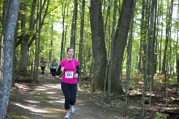 A female jogger jogging on a well beaten path, surrounded by trees and foliage. More students are also jogging on the path some distance behind her.