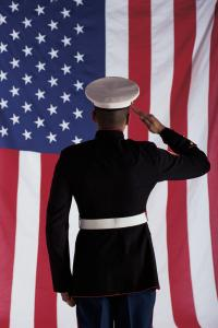 A marine, standing attention to the United States Flag