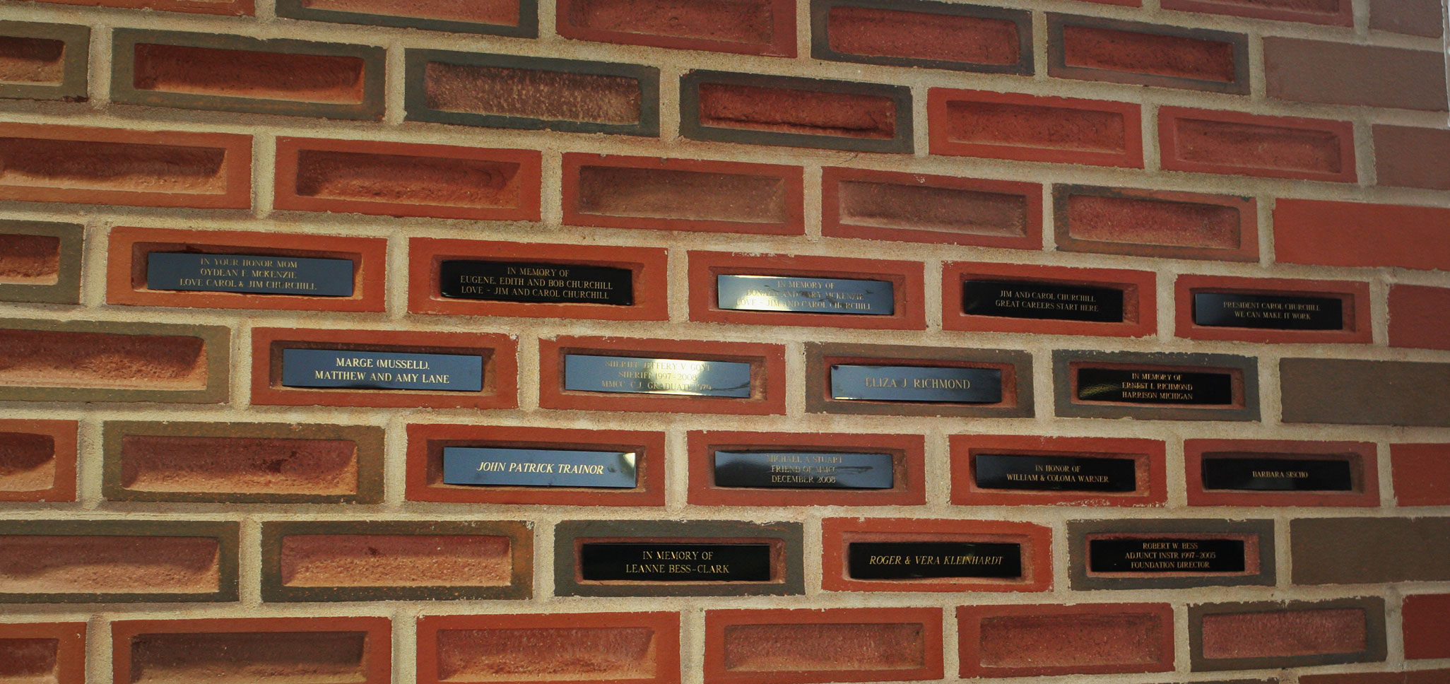A brick wall that holds multiple bricks with engraved placards on them. Some of them are memorials, some are the names of the donors themselves.