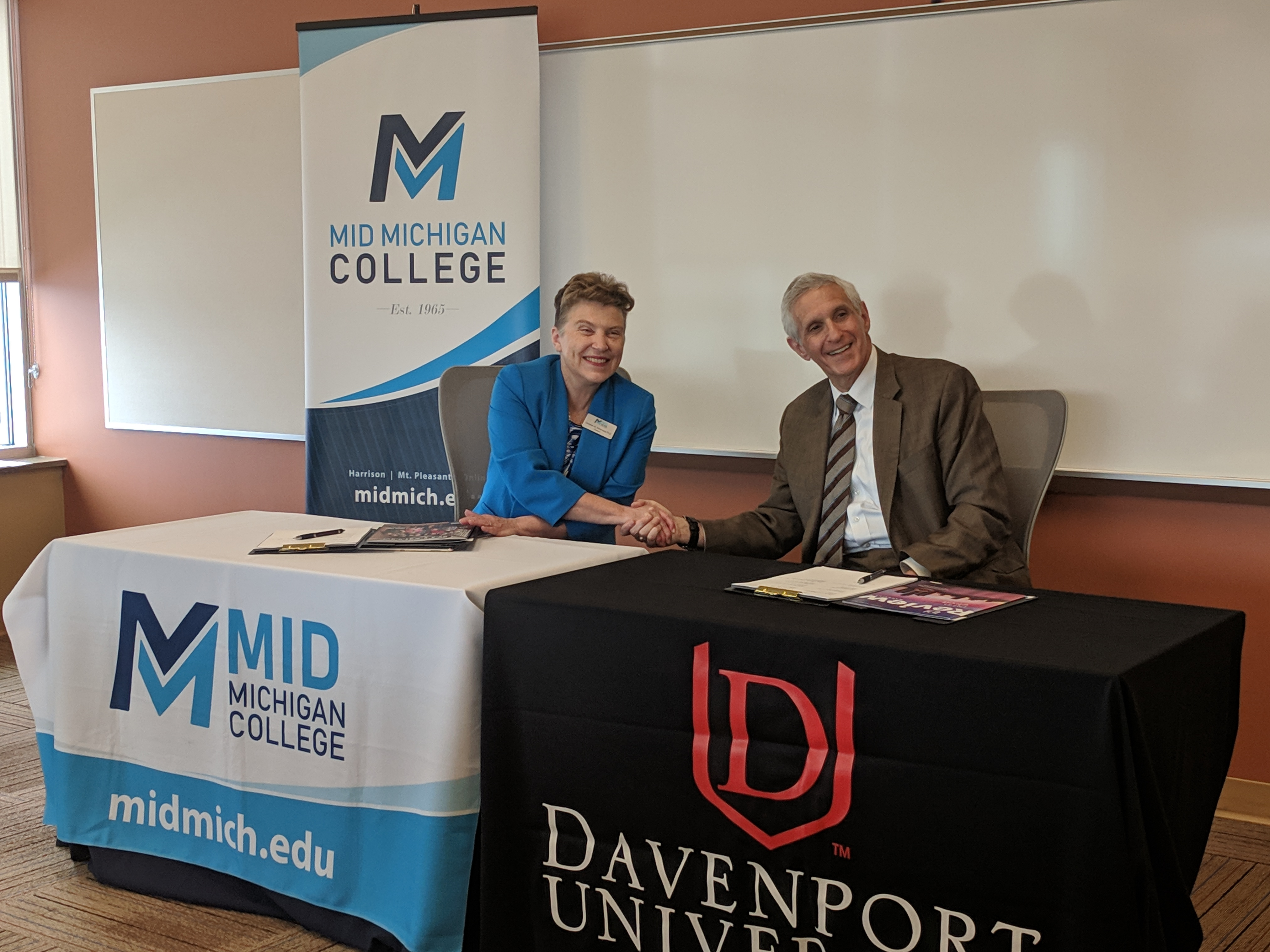 The Presidents of Mid Michigan College and Davenport University sign an academic agreement.