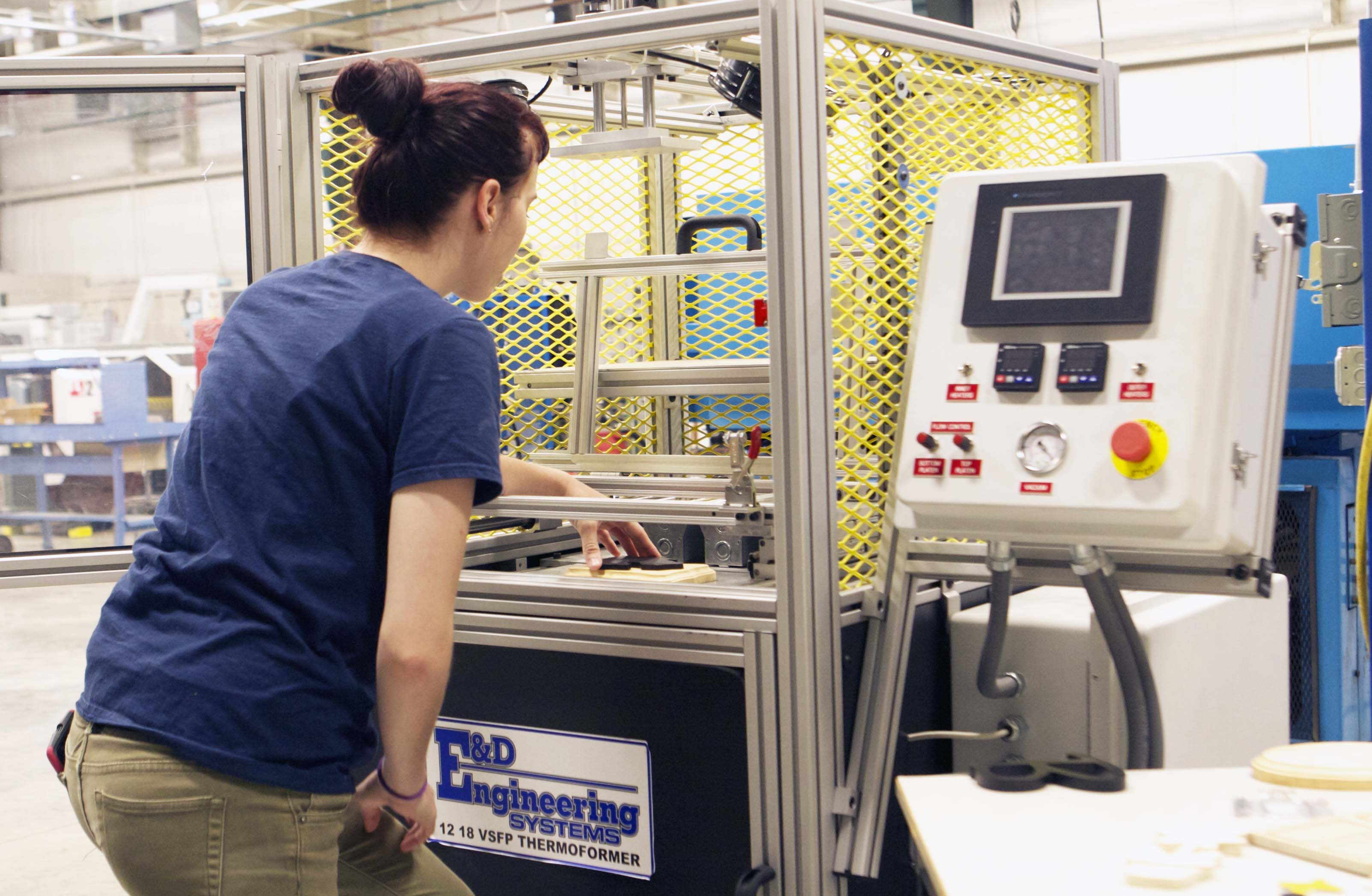 A student works on a thermoformer in the plastics lab.