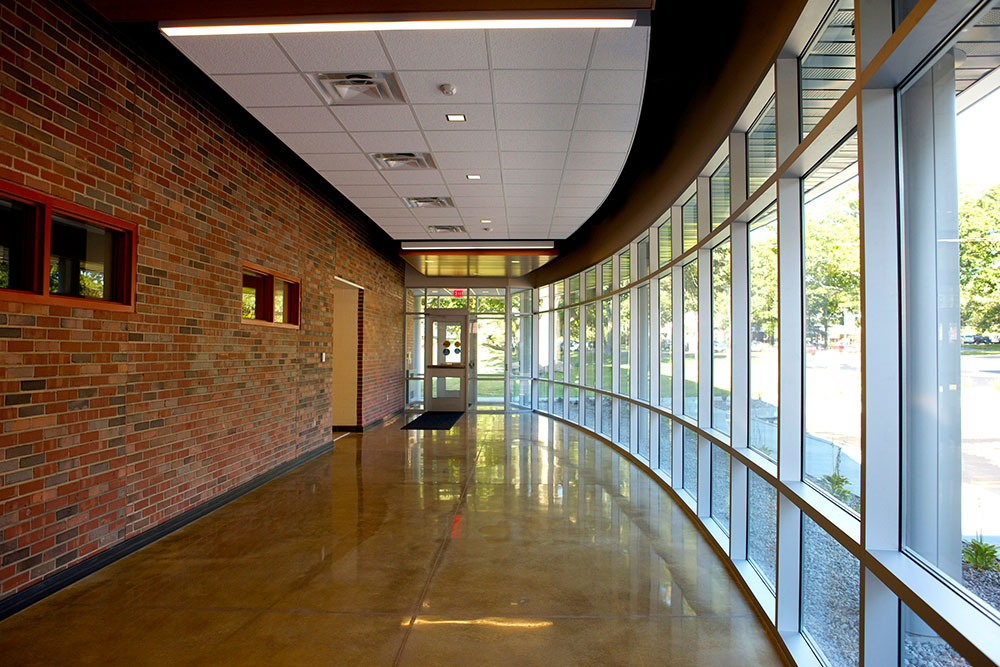 A large hallway with red brick lining the left wall, and the right side of the hallway is lined with large glass panes, curving towards the door at the end. It is sunny outside.