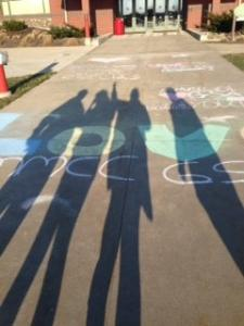 Four human shadows are cast over the words 'Love MMCC' written in chalk in front of the Doan Center in Mount Pleasant.
