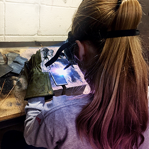A young woman learns how to weld in our Beginning Artistic welding class at Mid.