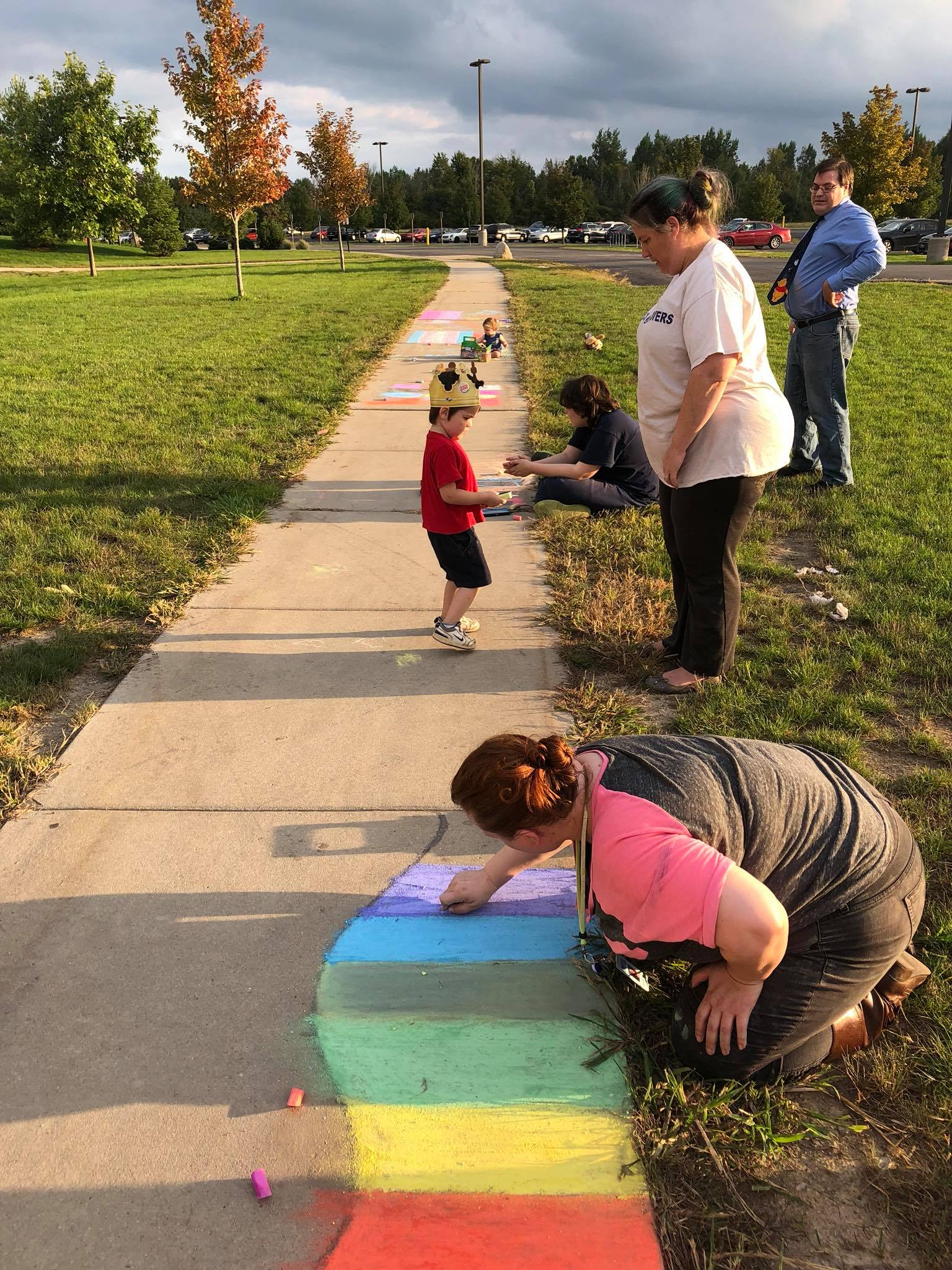Three adults, two teenagers, and two toddlers color the sidewalks on the Mount Pleasant campus for the pride celebration