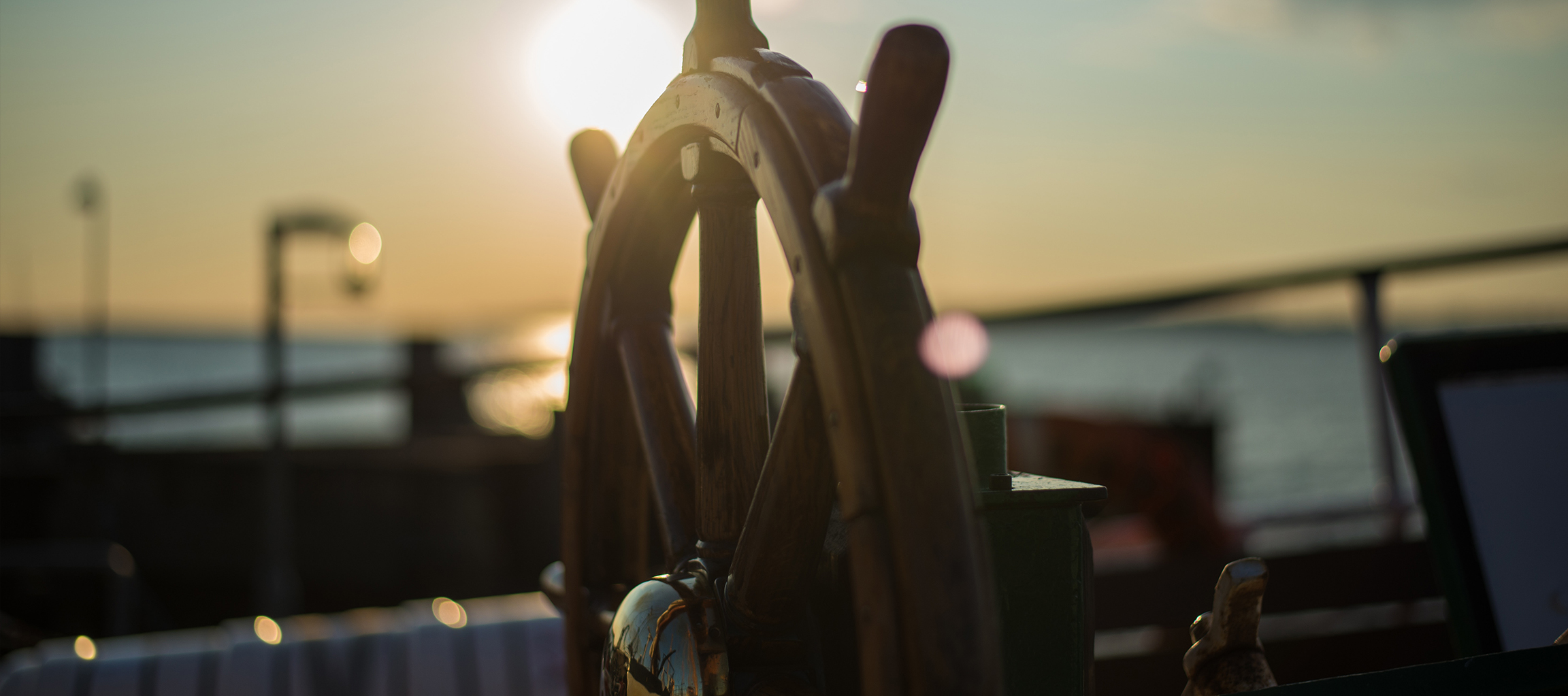 sunset image of a sailing ship's captains wheel