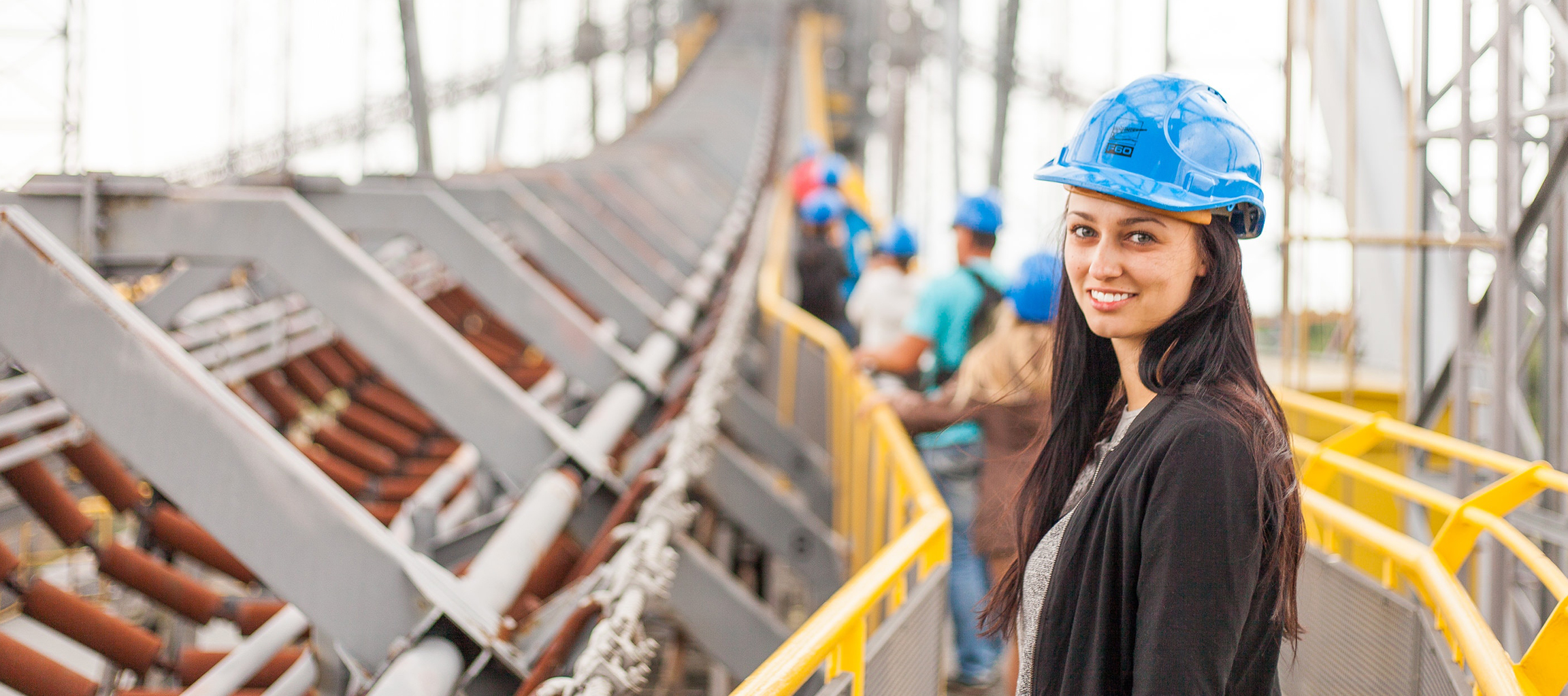 Confident young woman wearing a hard hat works in the field