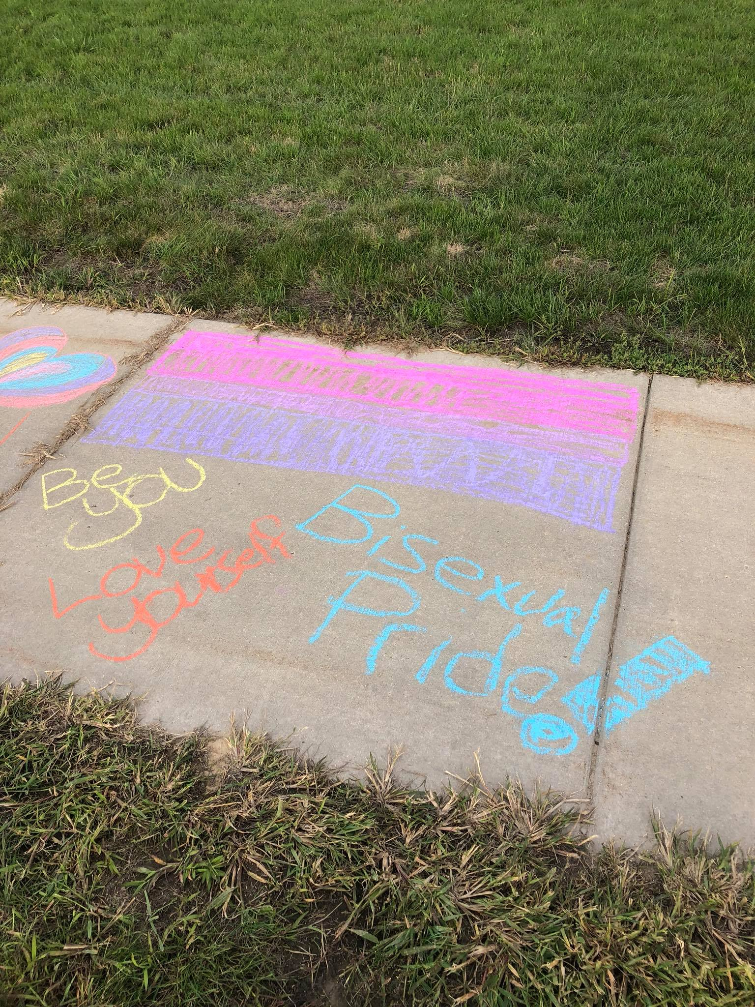 The pink, purple, and blue flag is drawn in chalk above the phrases: 'Be you', 'Love yourself', and 'Bisexual Pride!' on the Mount Pleasant campus sidewalk