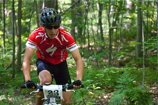 A male cyclist in a red jersey pedals on his mountain bike through the forest.