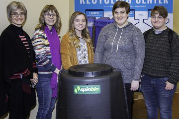 Mid Green committee member and student pose with composter.