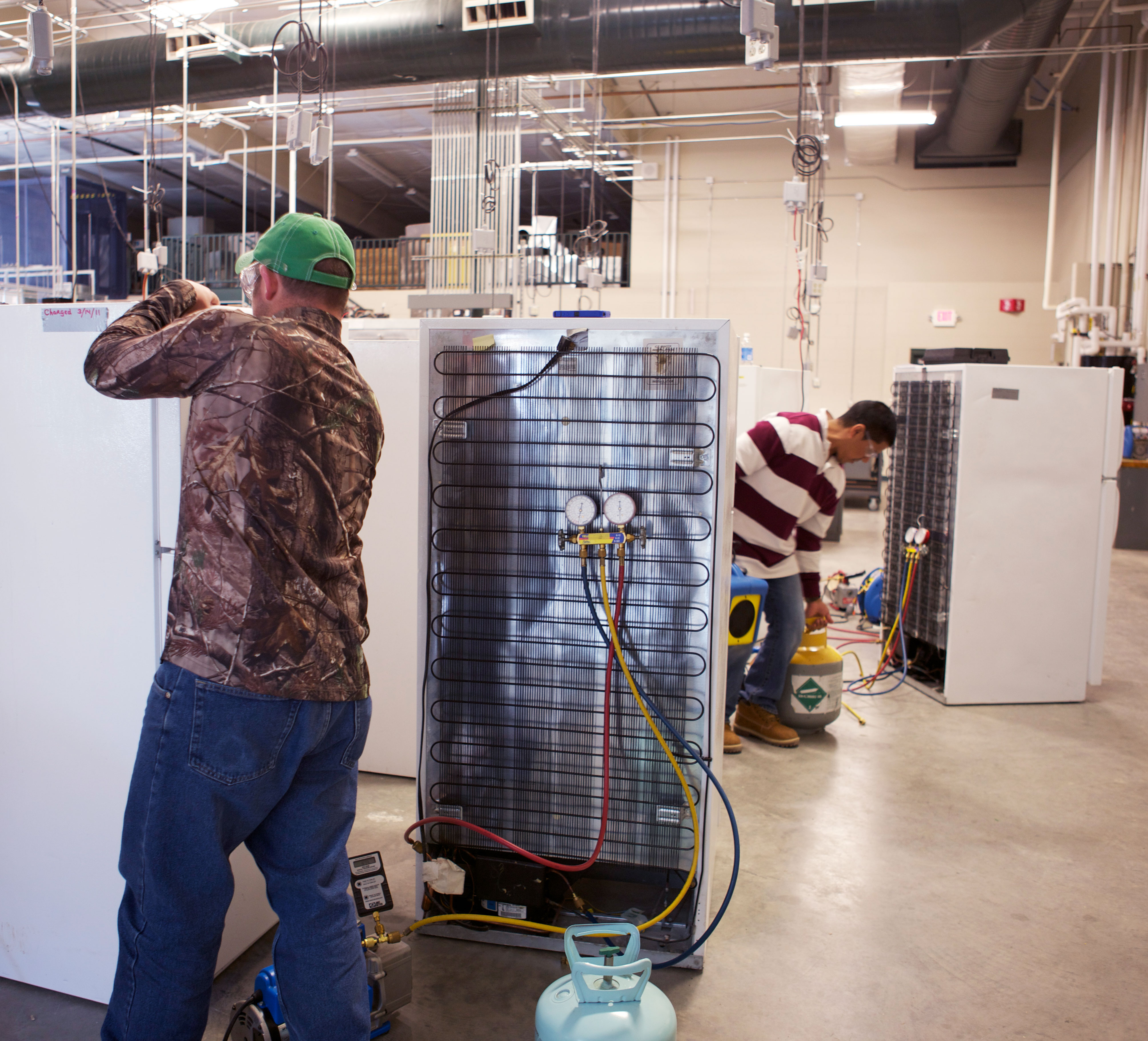 students working on residential refrigerators in a lab