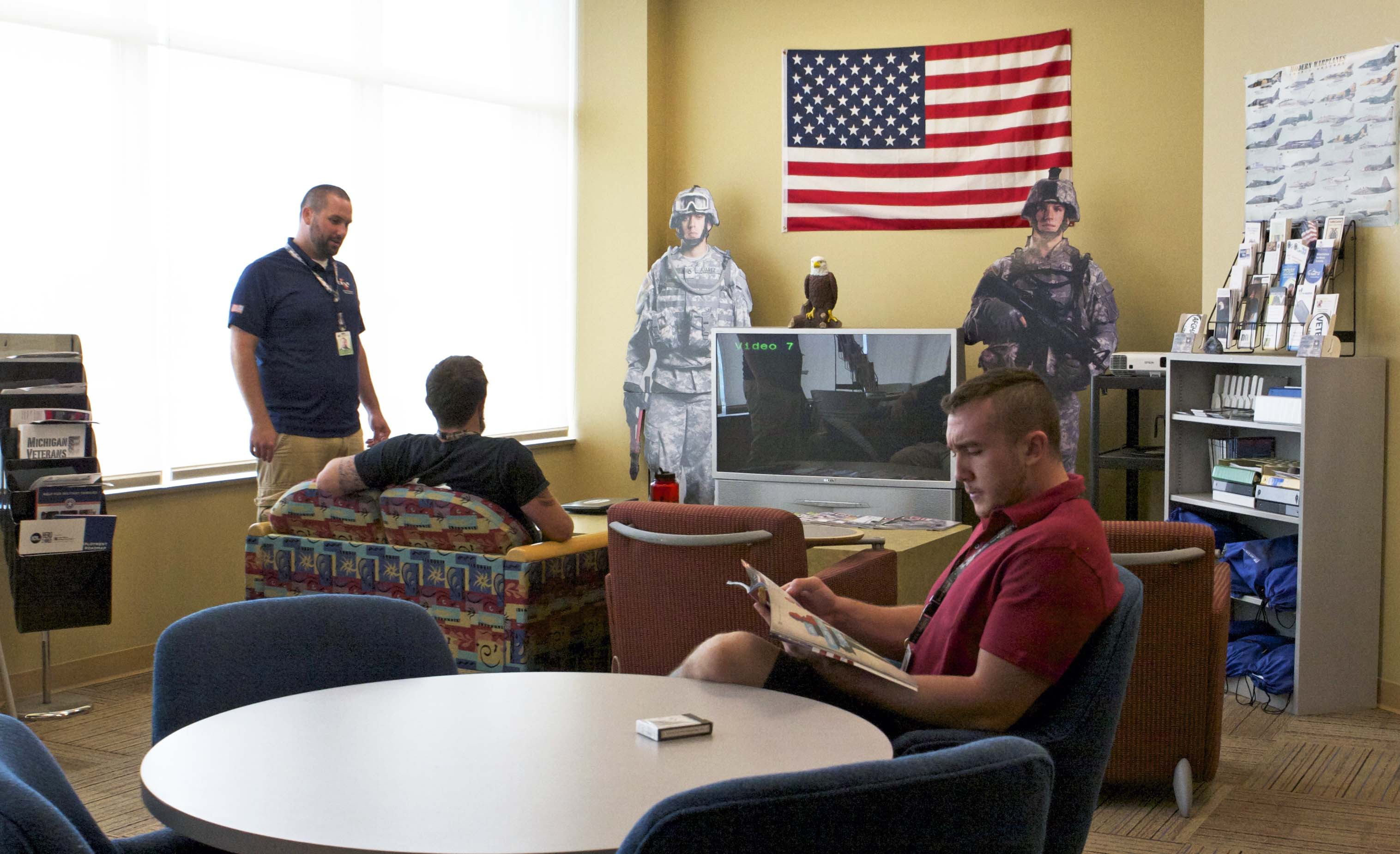 Student veterans relaxing in the Veterans Resource Center with their advisor. One student is reading a magazine