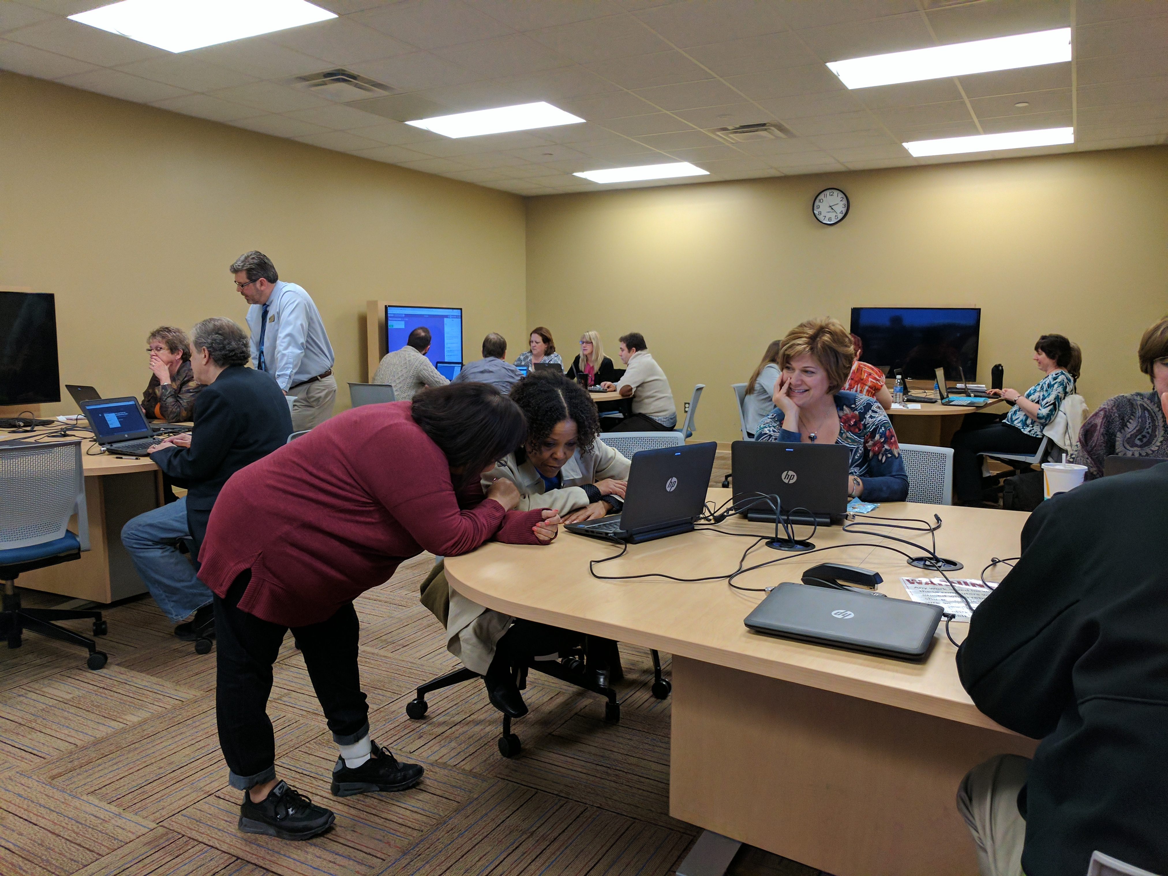 Classroom filled with employees working on laptops during a personal enrichment session