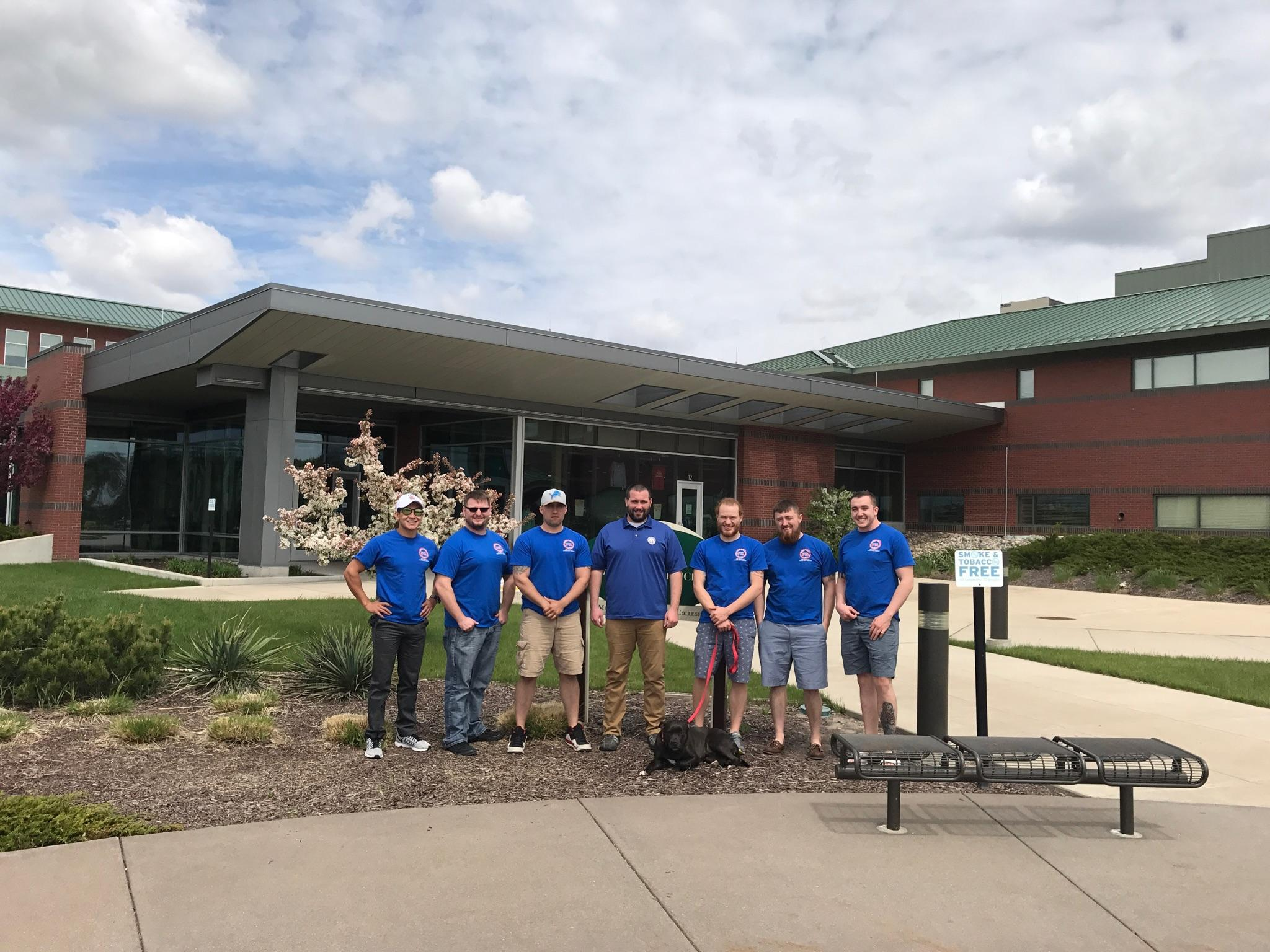 Seven members of the Student Veterans of America gather out front of the Mount Pleasant campus of Mid Michigan Community college with a large black dog on a leash. The members are all wearing their matching t-shirts.